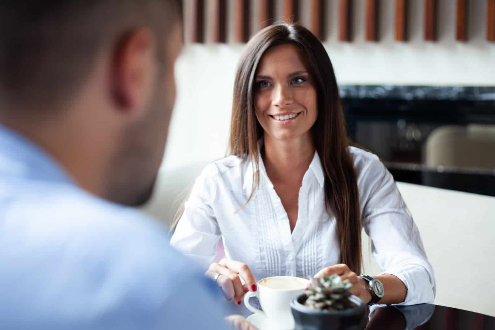 a smiling woman with long black hair is sitting at a table with a man and talking