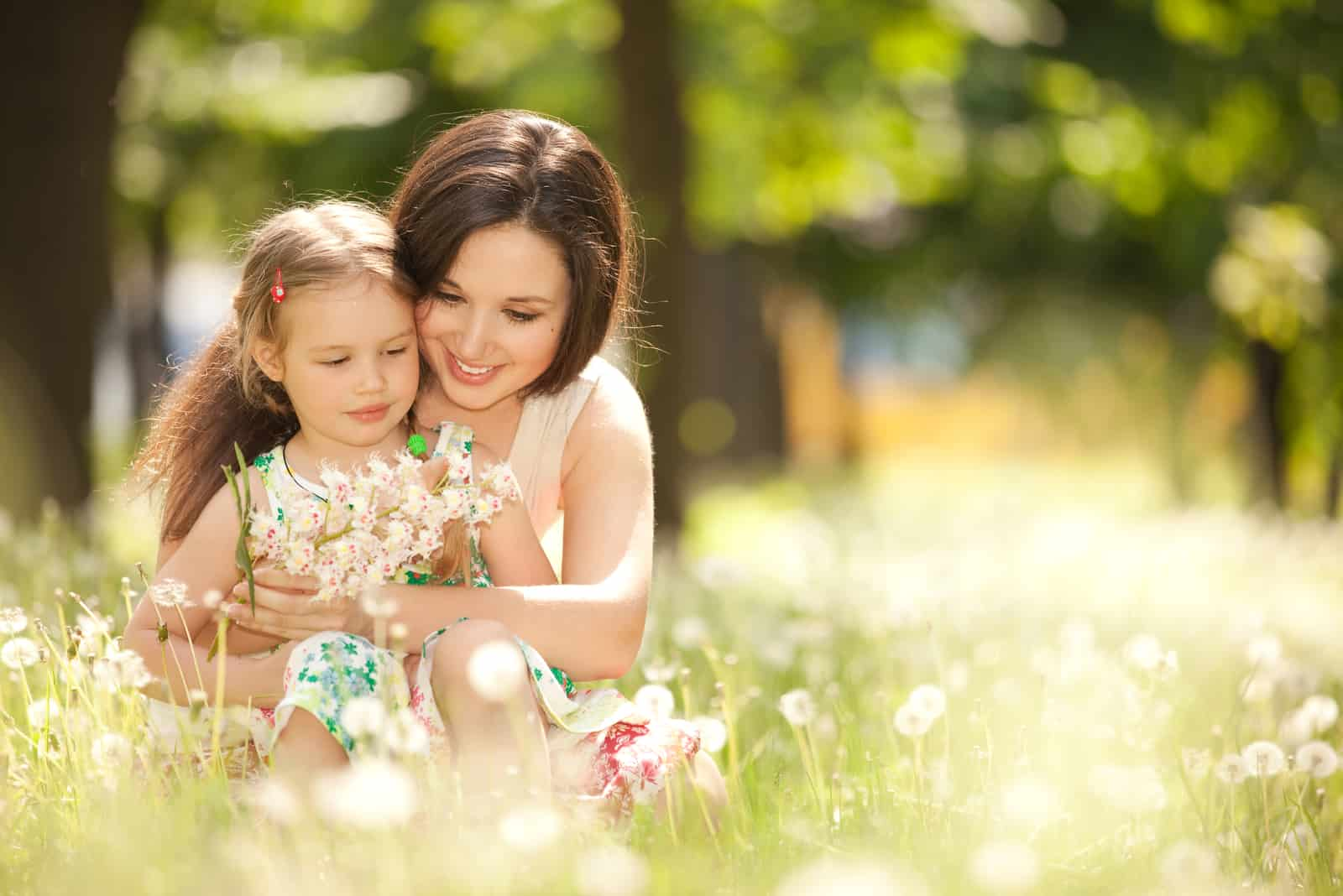 a woman sitting in the grass with a child