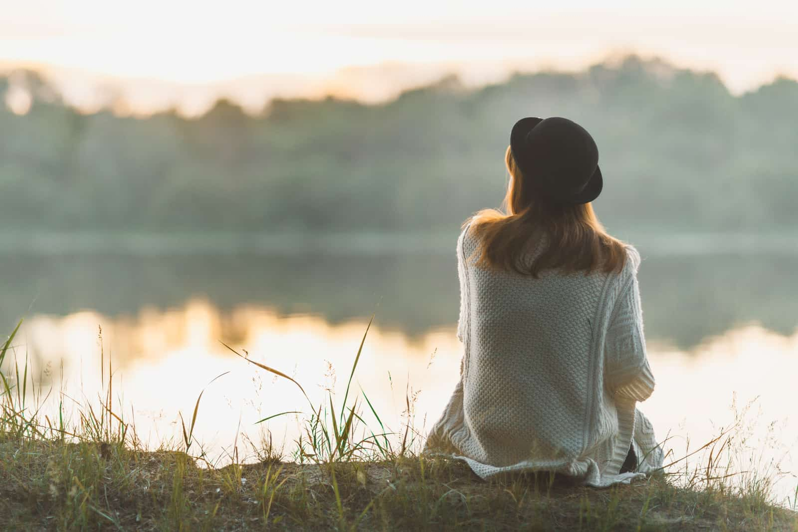 a woman with a hat on her head sits on the grass and looks out at the lake