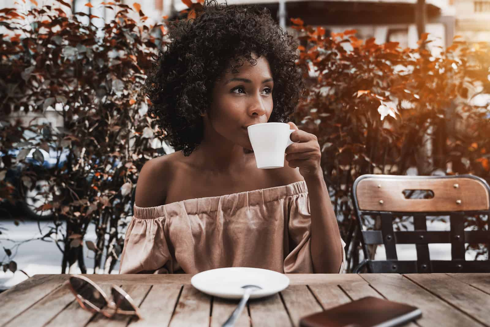 a woman with frizzy hair sits at a table drinking coffee and looks away