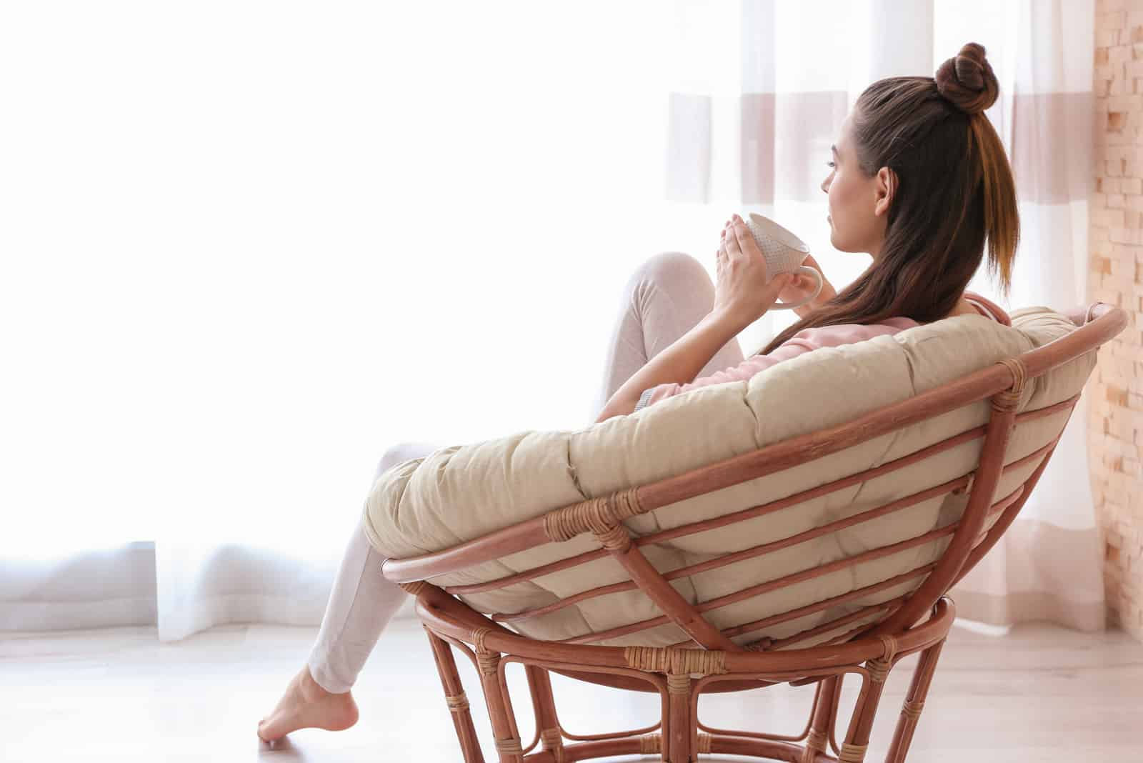 a woman with long black hair is sitting on a chair drinking coffee and looking in front of her