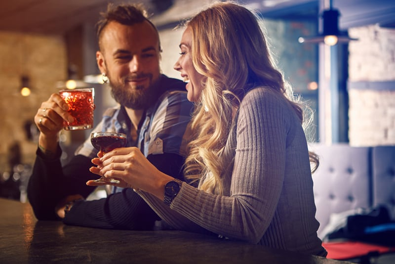 cheerful man and woman having drink together in the bar