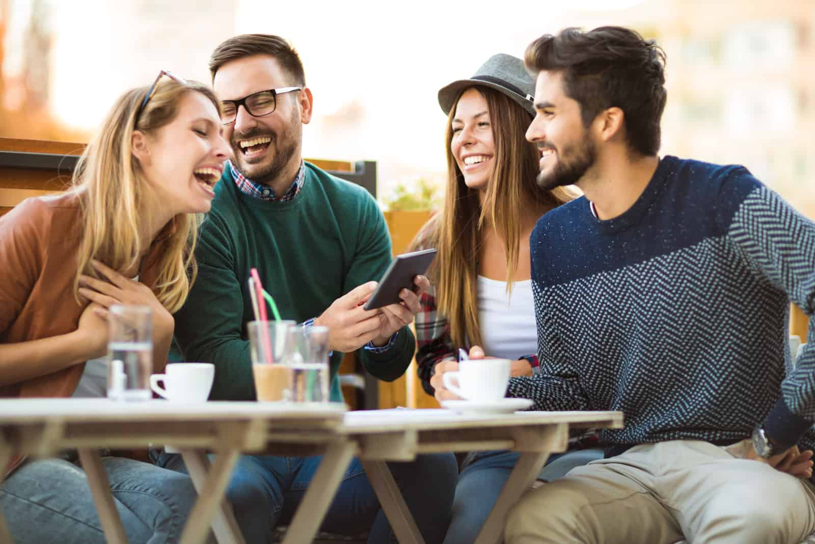 friends sit outdoors and laugh