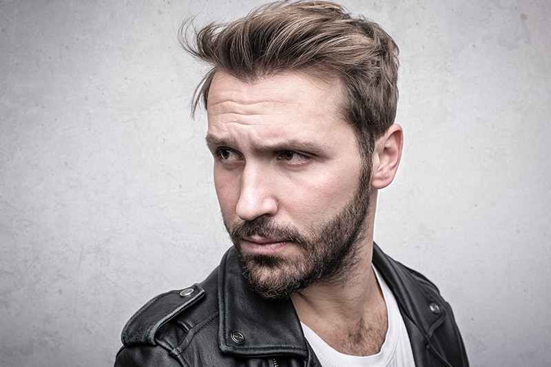 handsome bearded man in leather jacket looking aside
