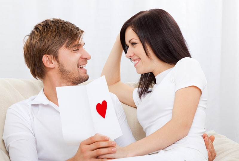 happy couple looking at each other holding greeting card