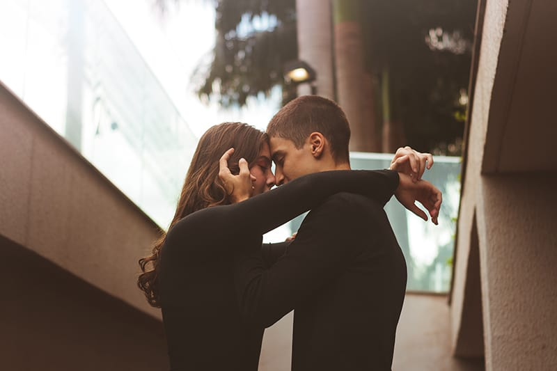loving couple hugging and cuddling while standing outside the building