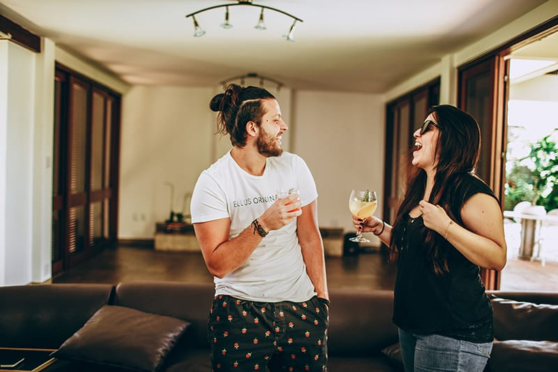 man and woman talking and laughing while having drinkg together at the party
