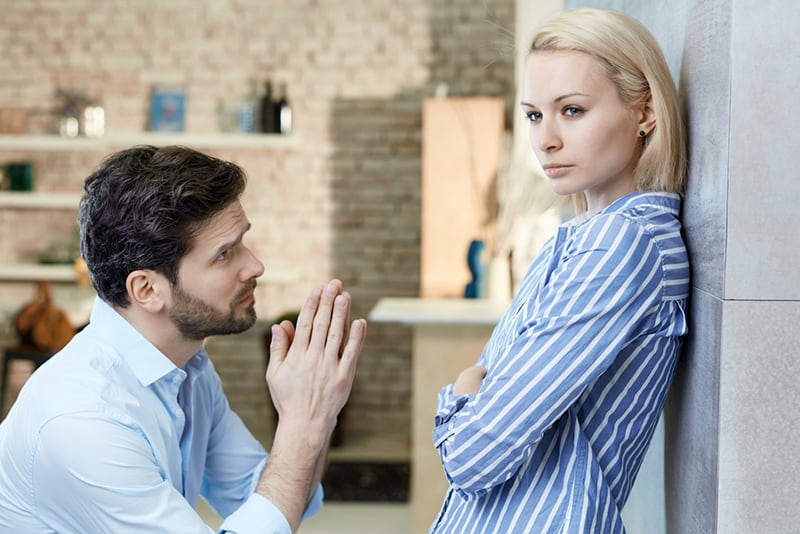 man asking sulky girlfriend's forgiveness at home on bended knees
