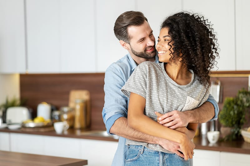 man embracing her wife from the back while standing in the kitchen