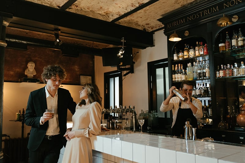 man flirting with a woman while leaning on the counter bar