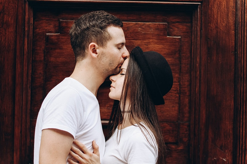 man kissing woman in the forehead while standing together near the door
