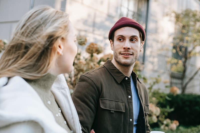 man looking at his girlfriend while walking together on the street
