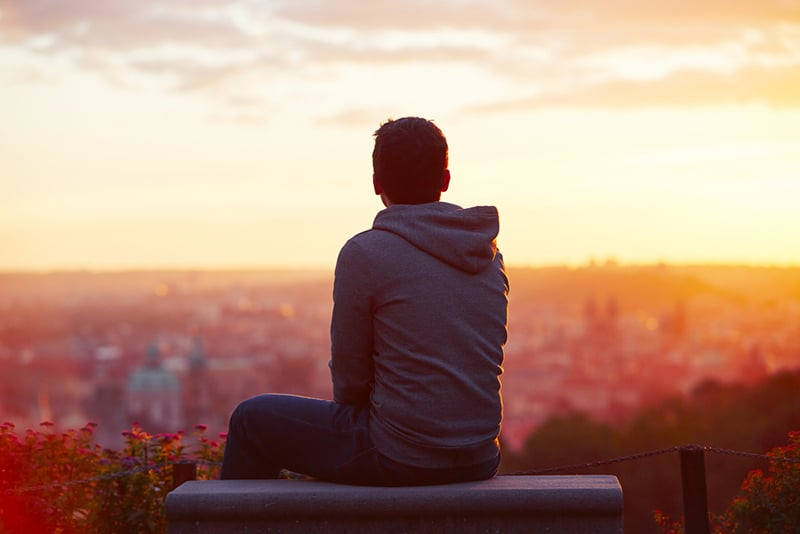 man looking at sunrise sitting on the bench