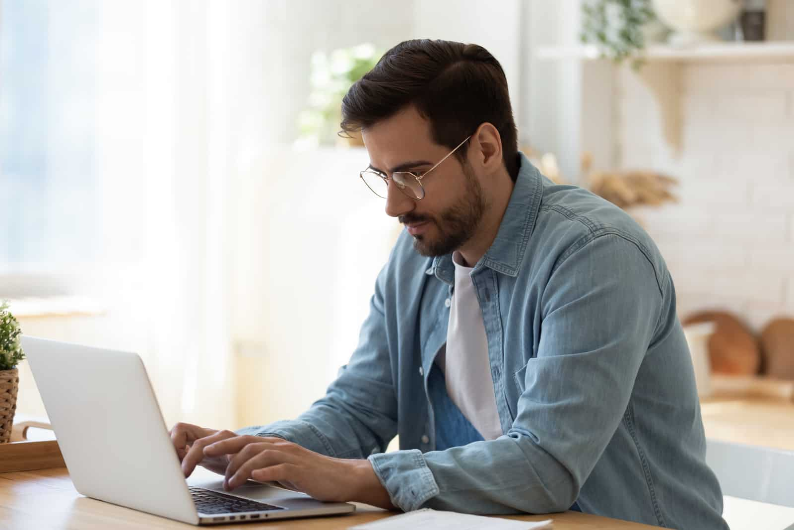 man sitting at wooden table and working on laptop