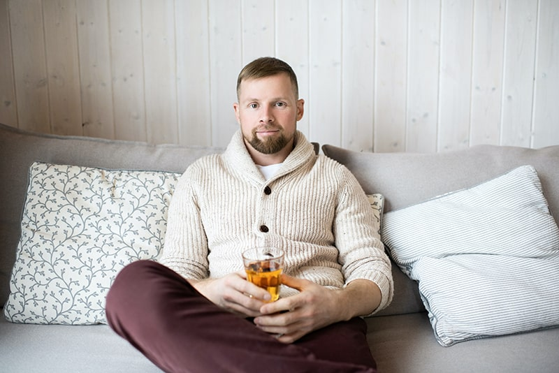 man sitting on the couch and holding glass with drink