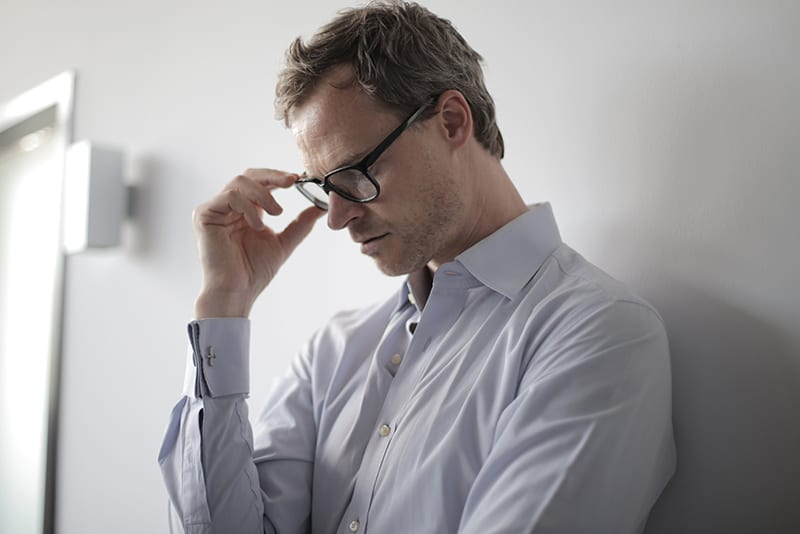 man touching eyeglasses with hand while leaning on the wall