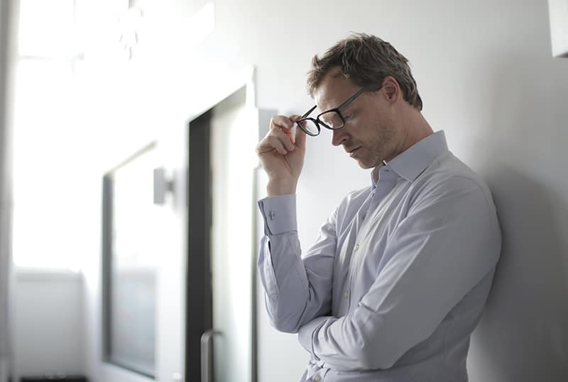 pensive man holding eyeglasses looking at floor