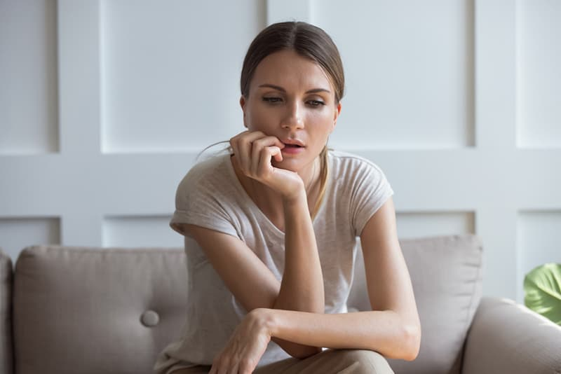 pensive woman sitting on the couch and looking at floor