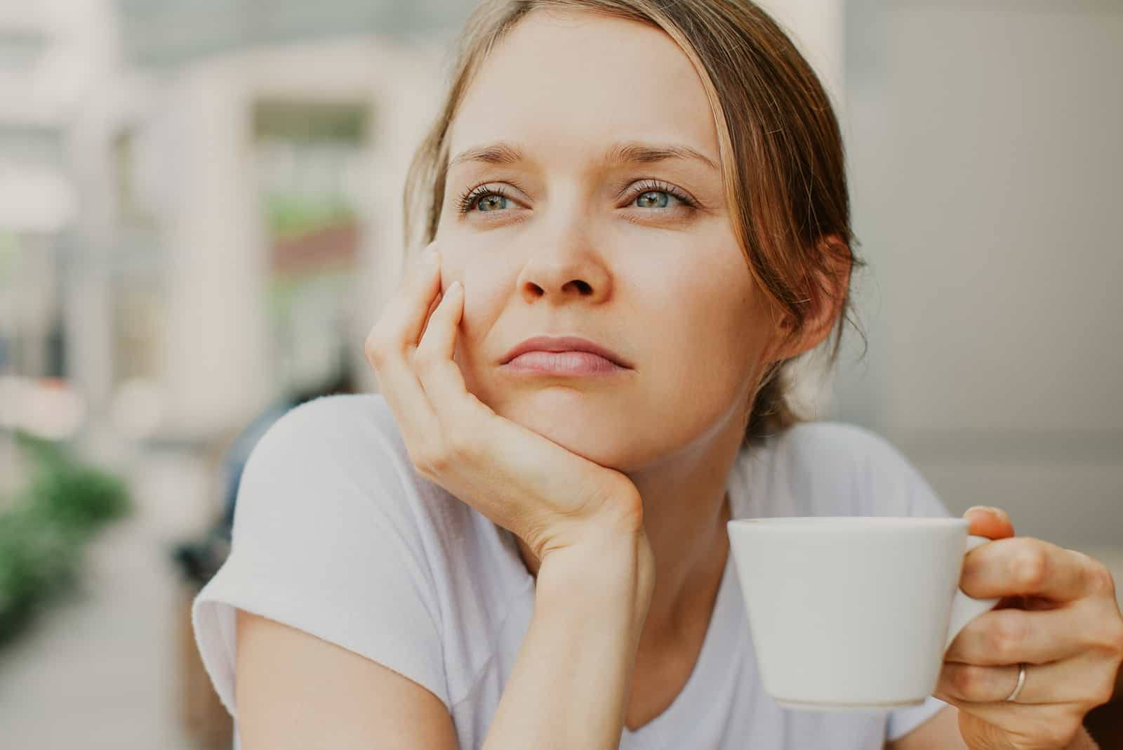pensive young beautiful woman drinking coffee outdoors