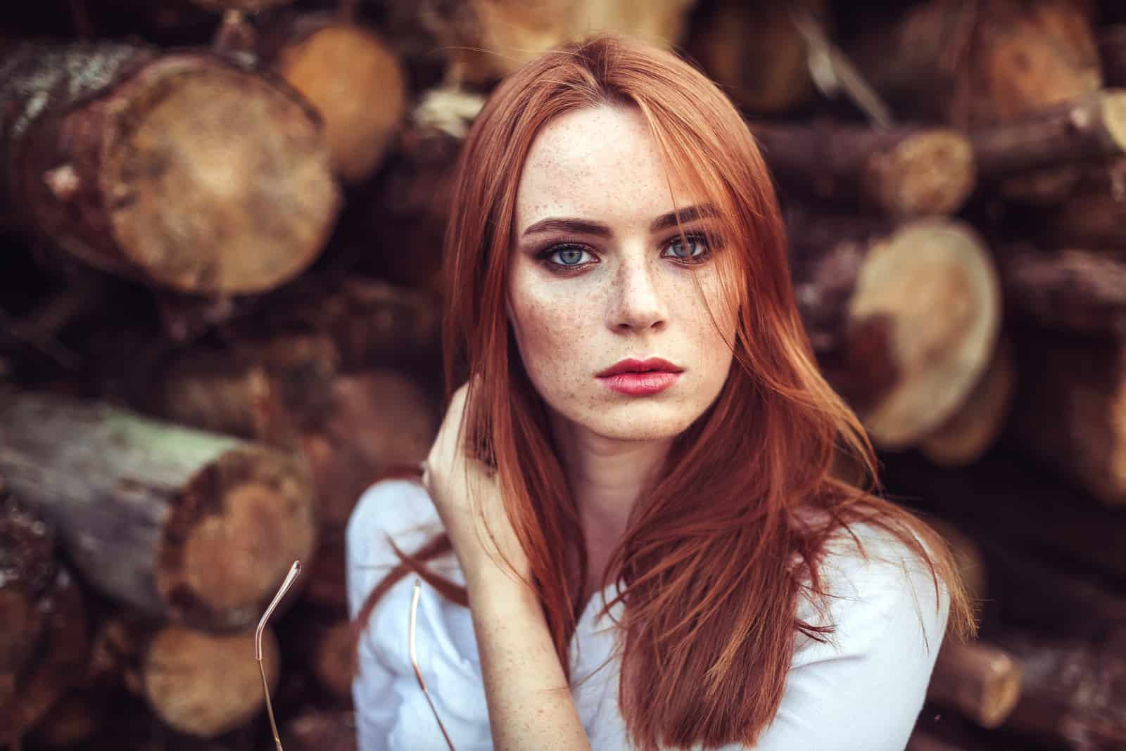 redhead young girl with healthy freckled skin wearing white top