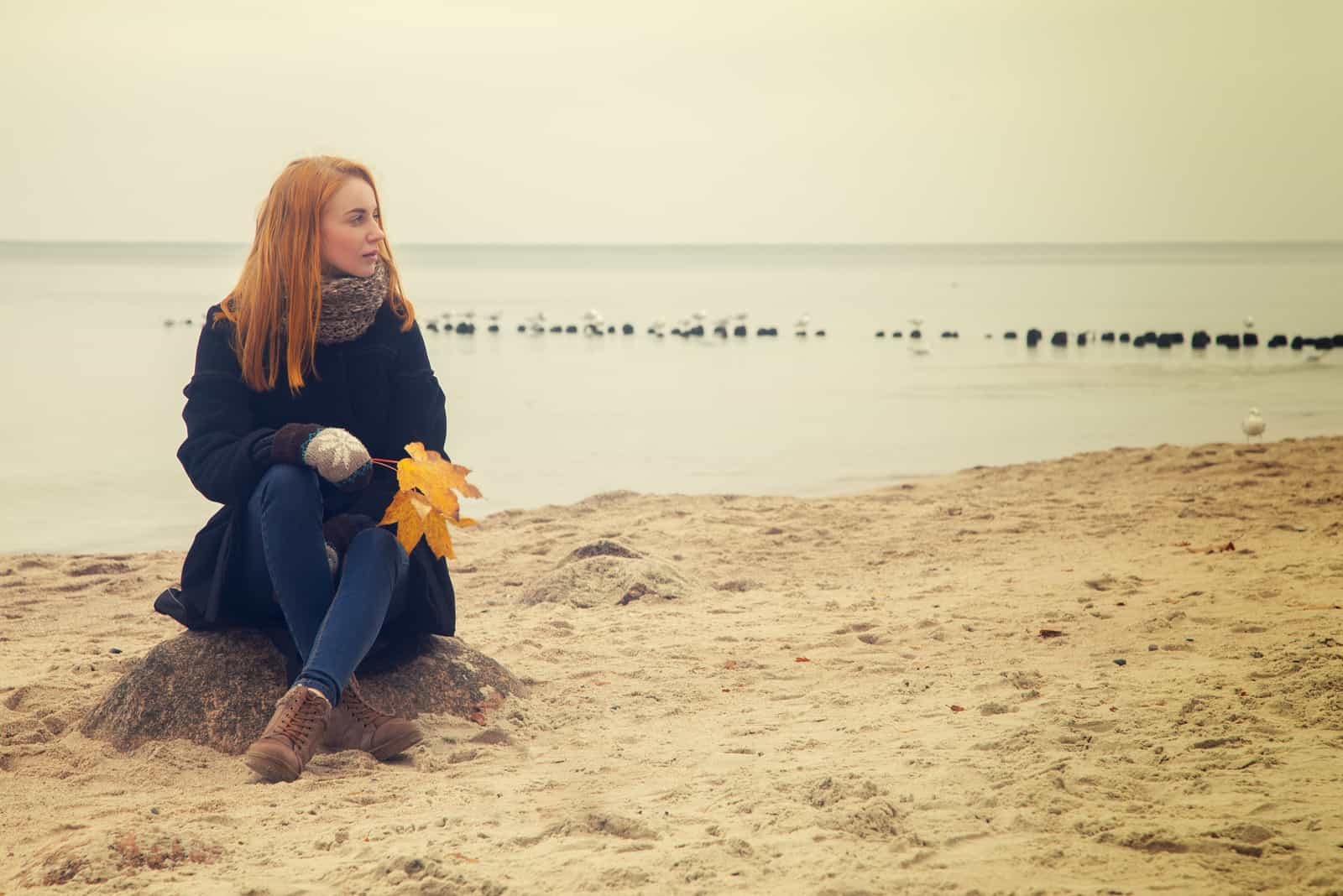 sad pensive woman on autumn sea beach sitting