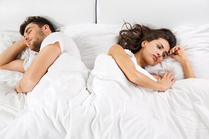 sad woman lying in the bed beside sleeping boyfriend