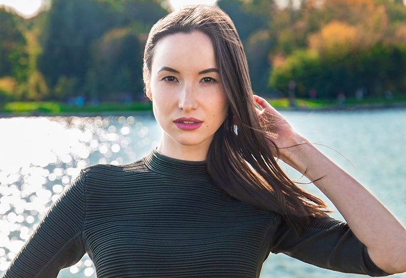 seductive woman with long black hair standing near the lake