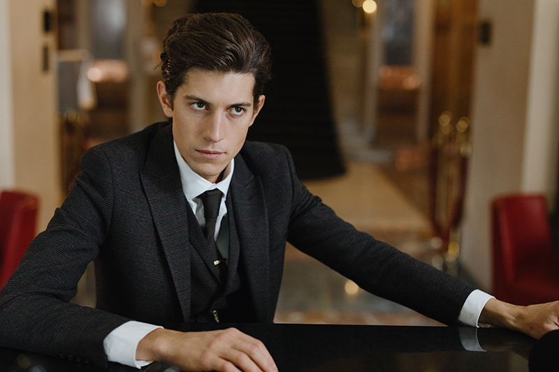 serious man in black suit sitting at the bar