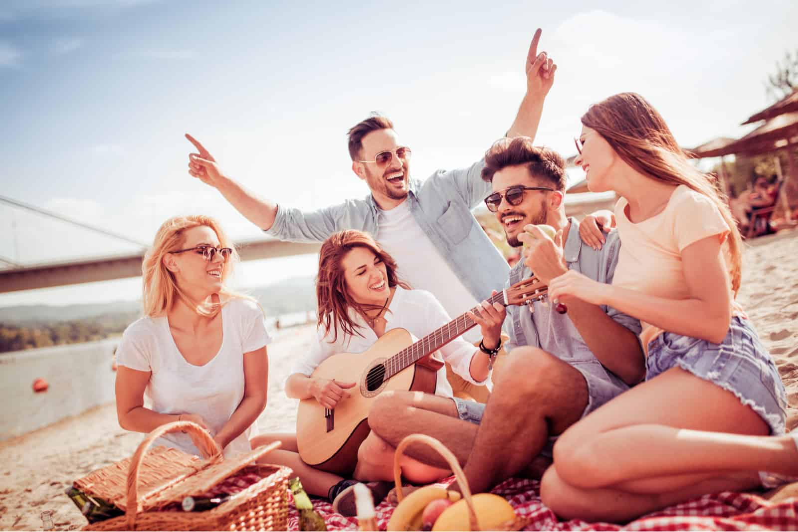 smiling friends sit on the beach and sing along to the guitar