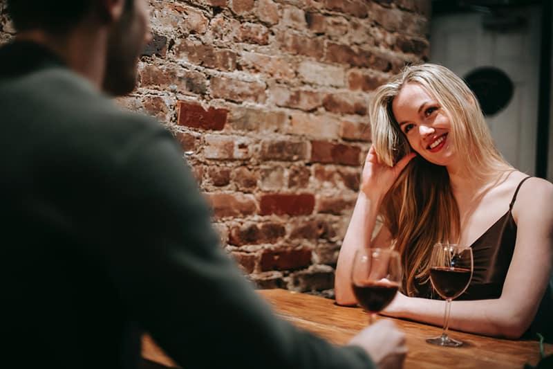 smiling woman sitting with her boyfriend in restaurant celebrating anniversary