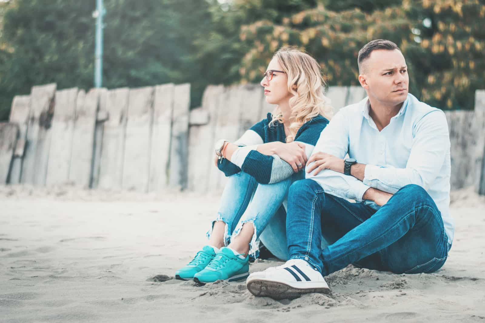the man turned his back on the woman as they sat on the beach