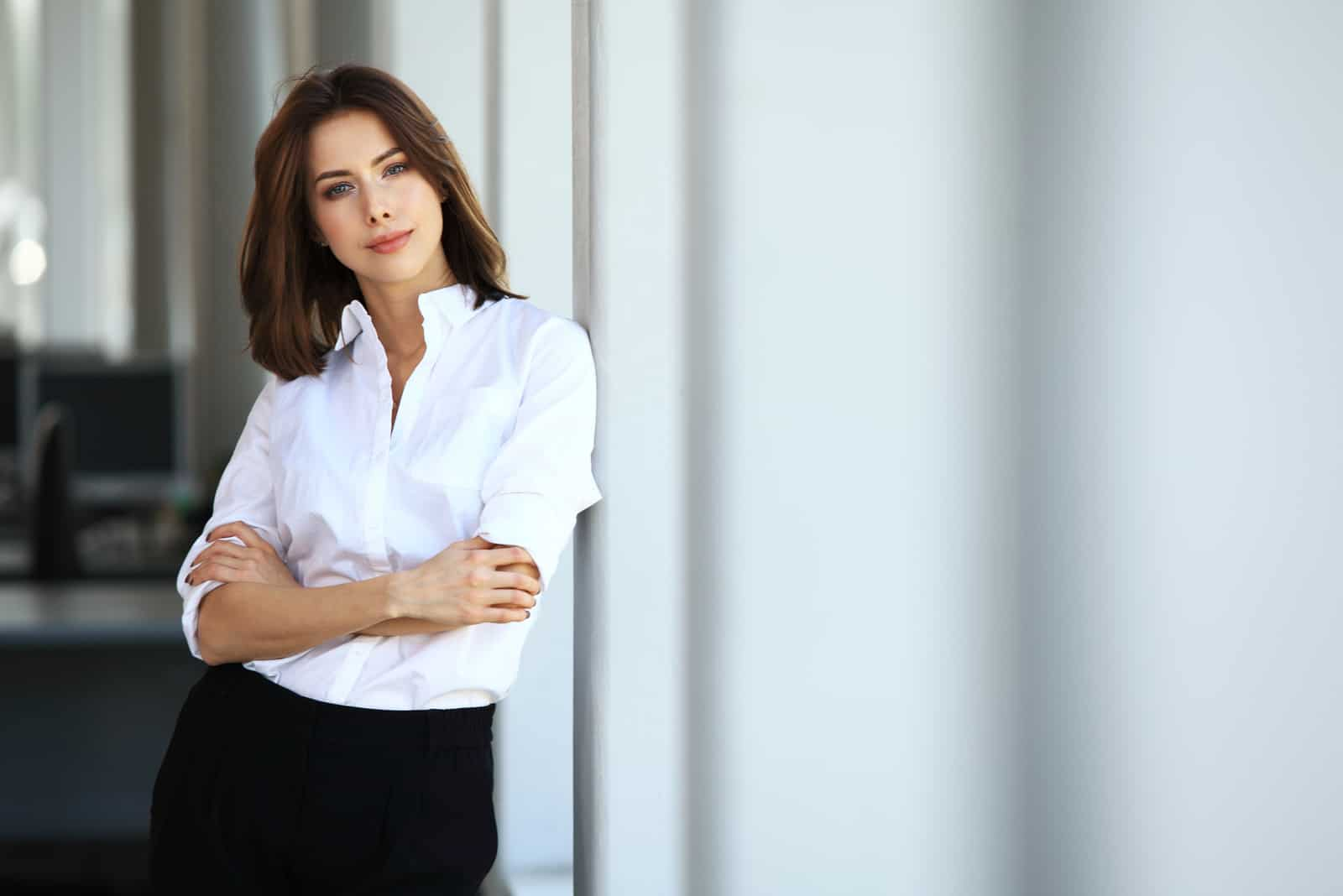 the woman stands leaning against the wall