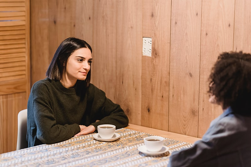 two female friends talking while drinking coffee at the table