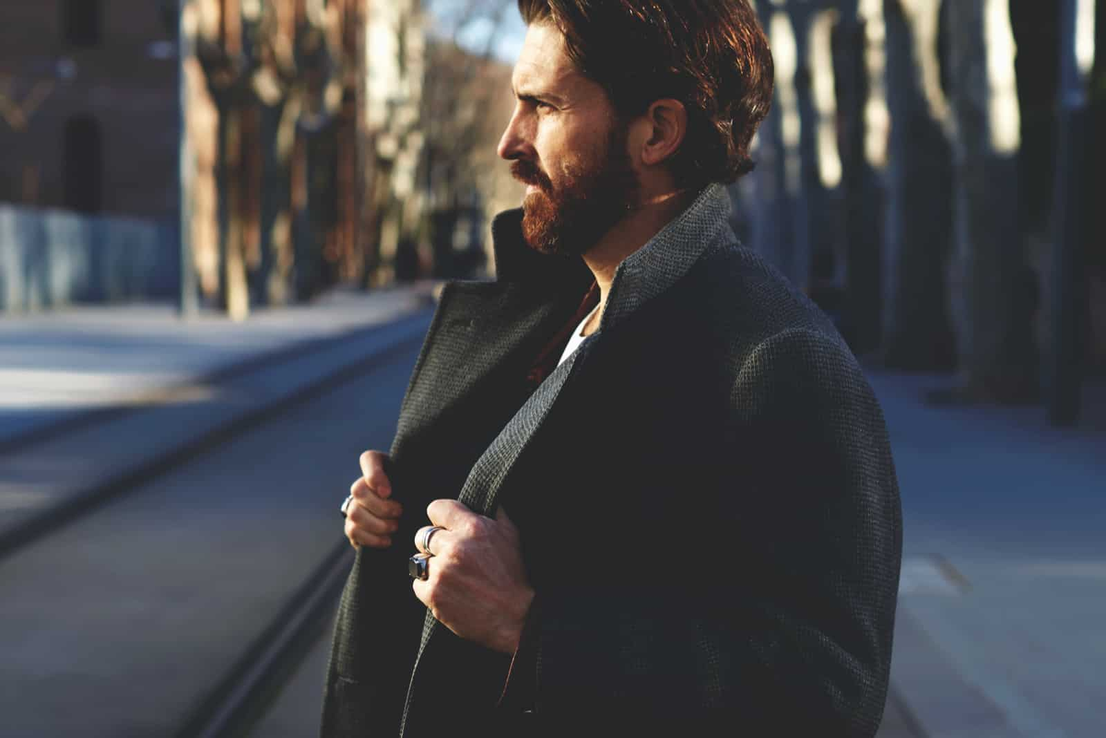 well dressed man with beard posing outdoors looking away