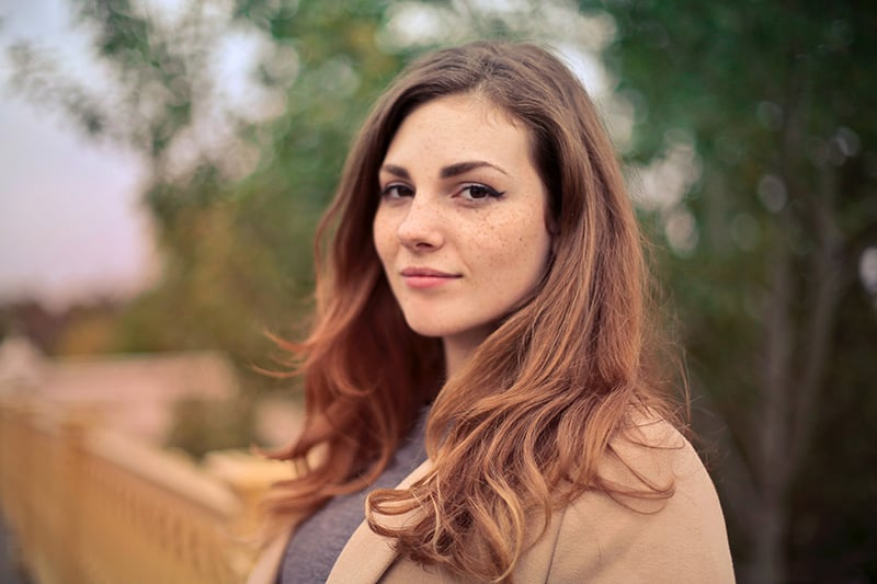 woman in brown coat standing outdoors