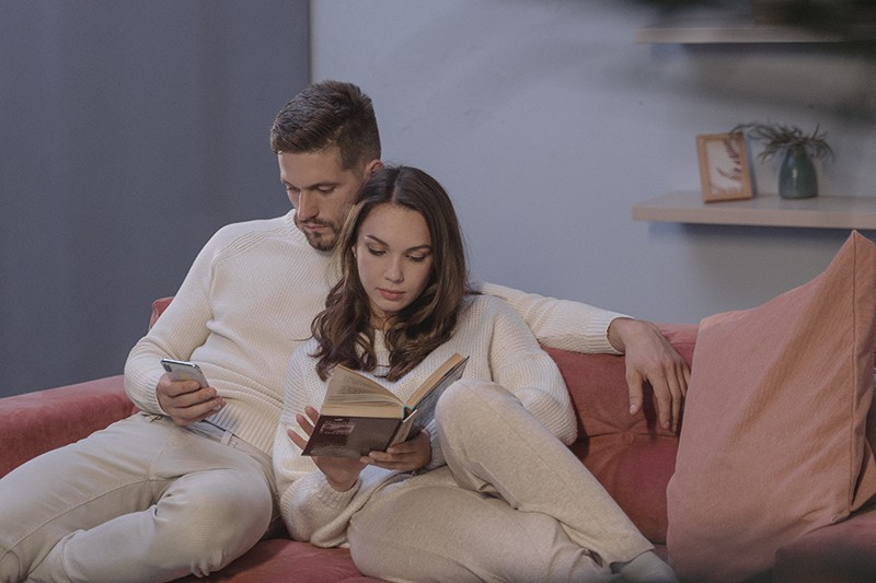 woman reading a book and man using his smartphone sitting on the couch close to each other