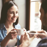 a smiling man and woman sit at a table and talk over coffee