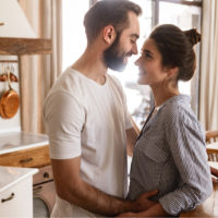 a man and a woman stand embracing in the kitchen
