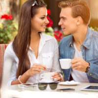 a smiling man and woman talking over coffee