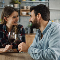 a man and a woman sit at a table and toast with wine