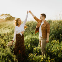 a man holds the hand of a woman in a field