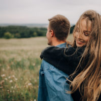 smiling woman hugging man from the back