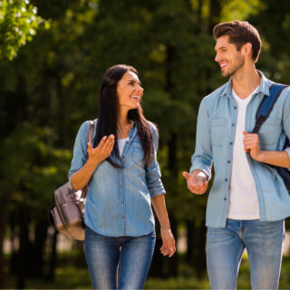 a smiling man and woman walk by