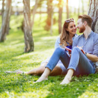 a man and a woman sit in the park and talk