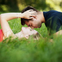 couple cuddling while lying on the grass
