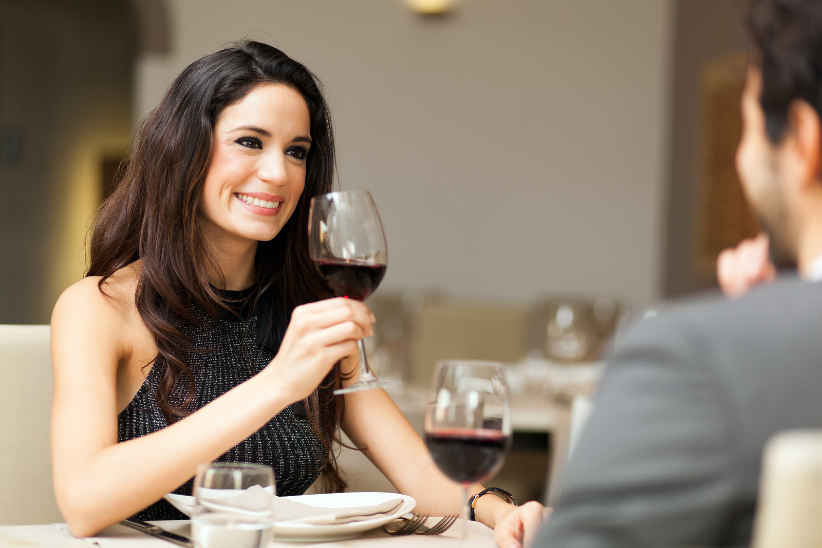 a black-haired woman holding a glass of wine and talking to a man