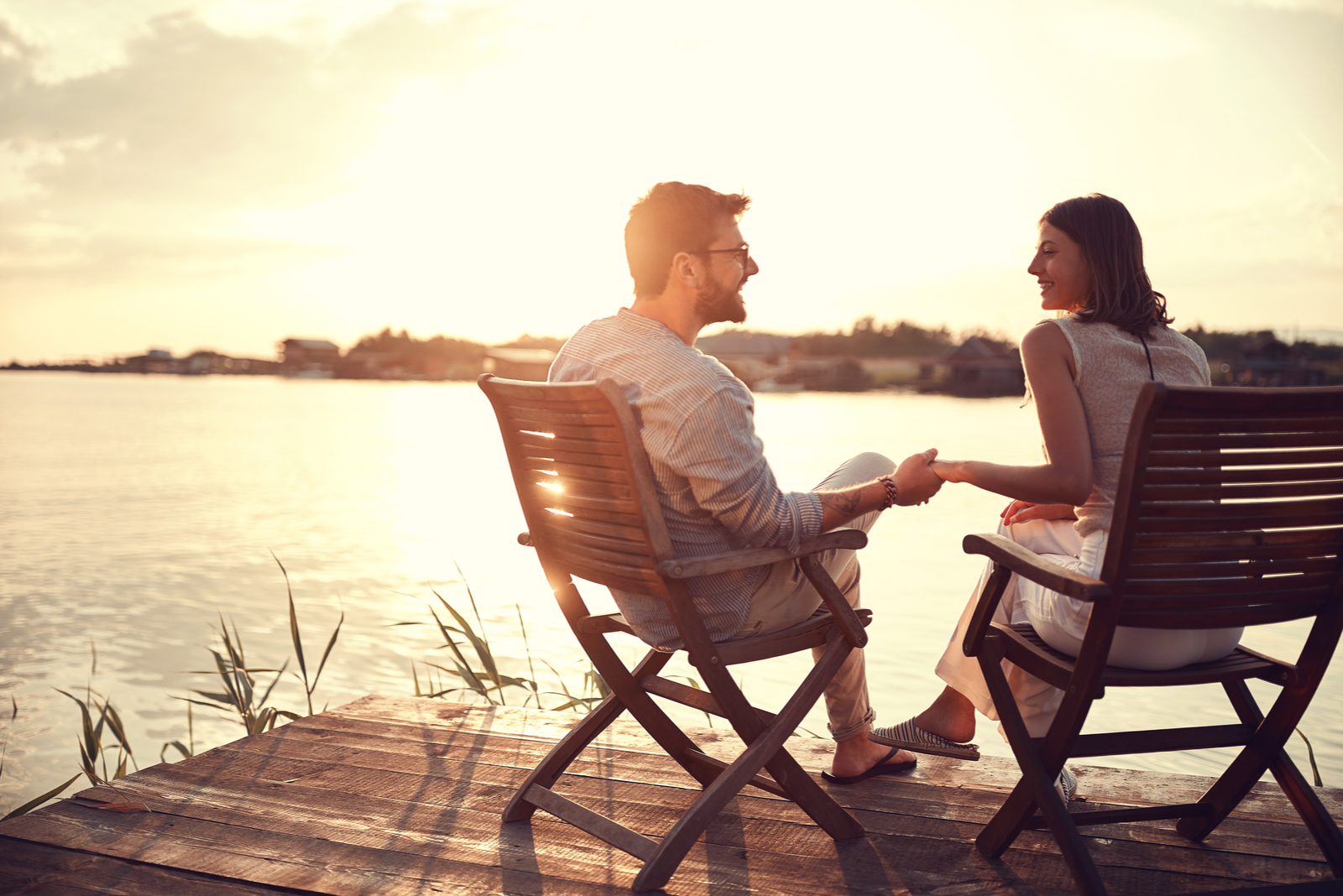 a man and a woman are sitting next to the pier holding hands