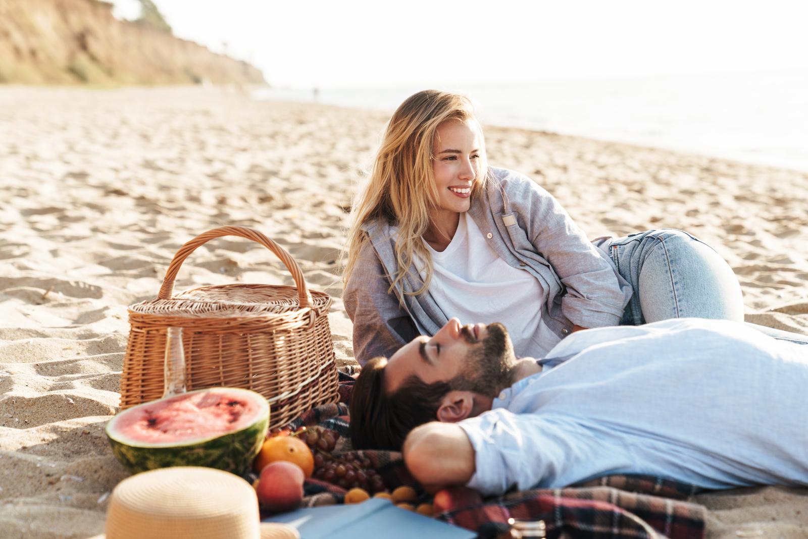a man and a woman lie on the beach