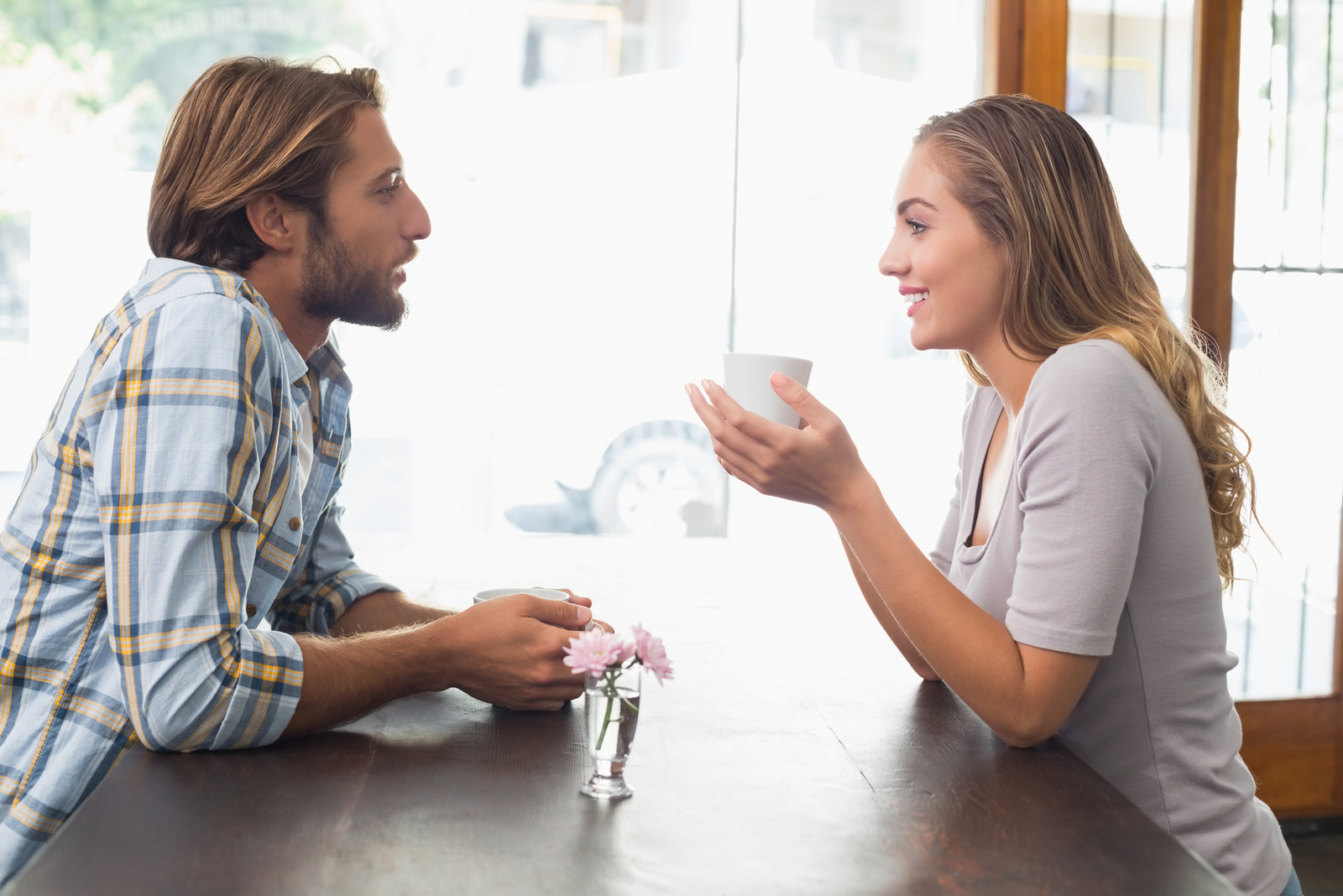a man and a woman sit at a table drinking coffee and talking