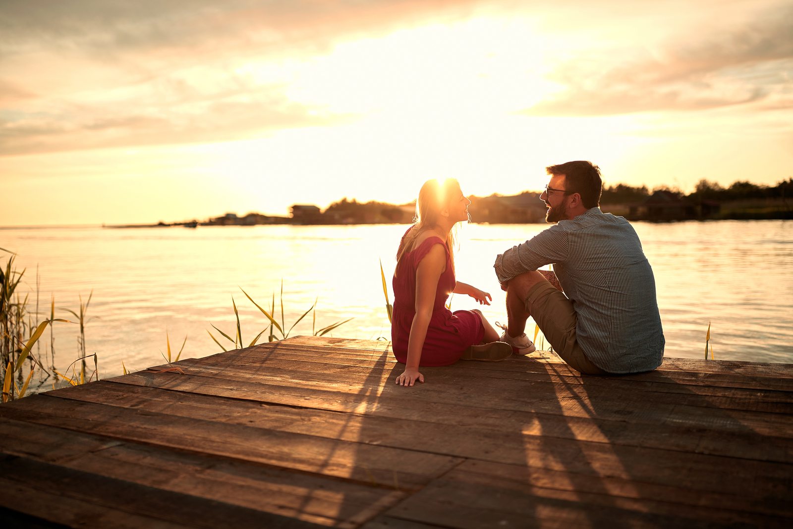 a man and a woman sit on the pier and talk